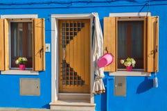 Casa blu con i fiori sui davanzali in Burano, Venezia fotografia stock