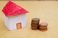 Casa bonita pequena com as moedas empilhadas na frente do fingimento modelo do alojamento: preços da habitação, compra de casa, r Foto de Stock Royalty Free