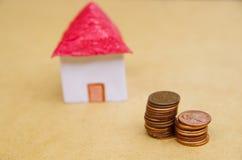 Casa bonita pequena com as moedas empilhadas na frente do fingimento modelo do alojamento:: preços da habitação, compra de casa,  Fotos de Stock