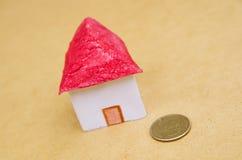 Casa bonita pequena com uma moeda na frente do fingimento modelo do alojamento: preços da habitação, compra de casa, bens imobili Imagens de Stock Royalty Free