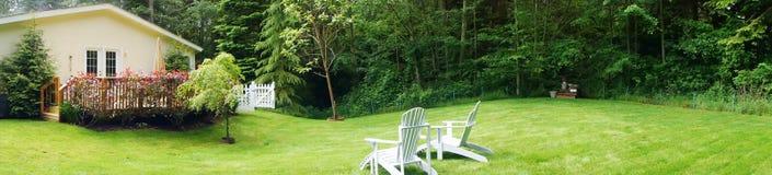 A casa branca adorável com poço manteve o gramado dianteiro Foto de Stock Royalty Free