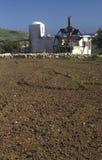 Casa branca com o moinho e o campo a cultivar Imagens de Stock Royalty Free