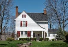 Casa branca da agitação com telhado repicado & os obturadores vermelhos Fotografia de Stock