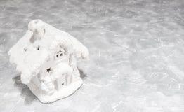 A casa branca do Natal pequeno do brinquedo está em um fundo cinzento Bens imobiliários, feriados, Natal, miniatura Lugar para o  foto de stock royalty free