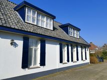 A casa branca do vintage com a janela azul aberta shutters, cortina de laço Fotografia de Stock Royalty Free