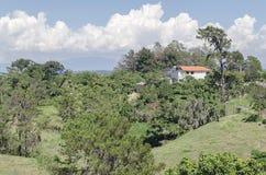 Casa branca nas montanhas, com céu azul e campos verdes imagem de stock