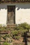Casa brasileira velha da exploração agrícola com os arbustos de madeira das etapas da pedra da porta Fotografia de Stock Royalty Free