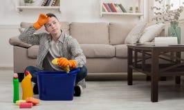 Casa cansado da limpeza do homem com detergentes Fotos de Stock Royalty Free