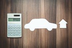 Casa, carro e calculadora de papel no fundo de madeira Engodo do negócio Fotografia de Stock