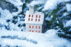 A casa cerâmica da lanterna com vela ardente no abeto coberto de neve ramifica no parque do inverno Imagens de Stock