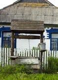 Casa cercana bien de madera vieja en pueblo De madera viejo bien con la ejecución del cubo en cadena Imagen de archivo