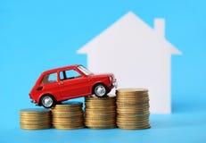 Casa, coche miniatura rojo y dinero Fotografía de archivo