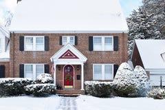 Casa colonial do tijolo com a porta vermelha arqueada nos feriados fotografia de stock royalty free