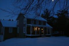 Casa colonial na noite com terra coberto de neve e lua que shinning acima dos membros de árvore foto de stock