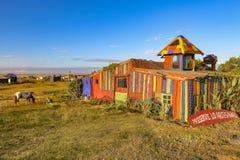 Casa coloreada en una playa, con un cielo azul y un caballo Imágenes de archivo libres de regalías