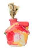 Casa colorida del moneybox con los dólares foto de archivo