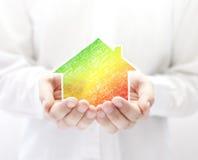 Casa colorida nas mãos Conceito da economia de energia Fotografia de Stock Royalty Free