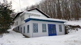 Casa com a grande garagem cercada com monte coberto de neve Fotografia de Stock