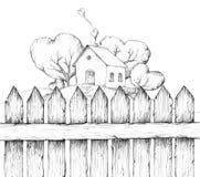 Casa com jardim atrás de uma cerca de madeira Fotos de Stock Royalty Free