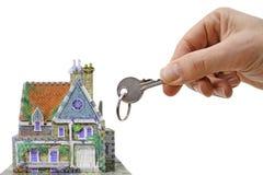 Casa com mão e chave Fotografia de Stock