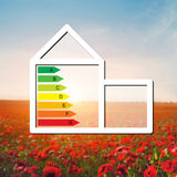 Casa com o sinal da economia de energia em um campo do fundo com Imagem de Stock Royalty Free