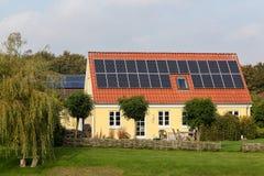 Casa com os painéis solares no telhado Imagens de Stock Royalty Free