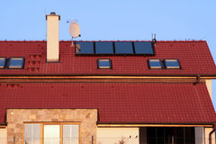 Casa com os painéis solares no telhado para o aquecimento de água Fotografia de Stock