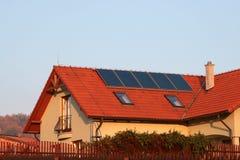 Casa com os painéis solares no telhado para o aquecimento de água Imagem de Stock