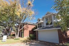 Casa com a casa para o sinal da jarda da venda e a folhagem de outono colorida dentro fotografia de stock royalty free