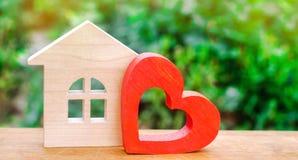 Casa com um coração de madeira vermelho Casa dos amantes Alojamento disponível para famílias novas Casa do dia do ` s do Valentim foto de stock royalty free