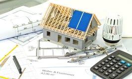 Casa com um plano da construção e um planeamento do painel solar foto de stock royalty free