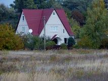 Casa com um telhado vermelho perto da floresta fotos de stock royalty free
