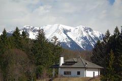 Casa con el fondo capsulado nieve de la montaña Fotografía de archivo libre de regalías