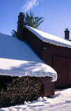 Casa con humo de la chimenea y la pila de madera Imágenes de archivo libres de regalías