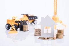 Casa con i soldi della moneta del mucchio e l'industria dell'edilizia di affari Fotografie Stock Libere da Diritti