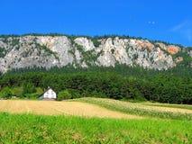 casa con il campo sotto la roccia   Immagini Stock Libere da Diritti
