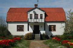Casa con la azotea y el jardín rojos Foto de archivo libre de regalías
