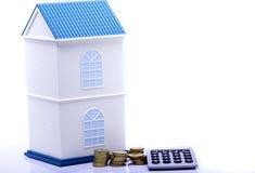 Casa con la moneta ed il calcolatore Fotografie Stock Libere da Diritti