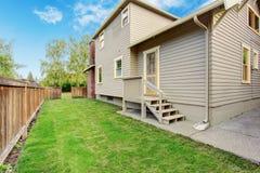 Casa con la pequeños cubierta y patio trasero Imágenes de archivo libres de regalías