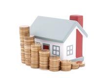 Casa con la pila de monedas Foto de archivo libre de regalías