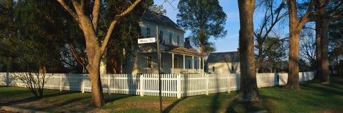 Casa con la rete fissa di picchetto bianca sulla via principale Fotografia Stock
