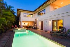 Casa con lo stagno e vasca calda al tramonto Fotografia Stock