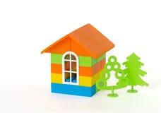 Casa con los árboles verdes hechos de ladrillos plásticos Aislado en el fondo blanco Foto de archivo