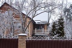 Casa con los árboles y los abetos en invierno de la nieve Fotografía de archivo libre de regalías