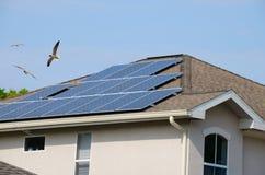 Casa con los paneles solares y los pájaros de vuelo Fotografía de archivo libre de regalías