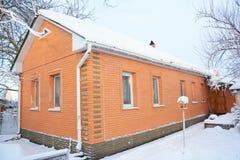 Casa con mattoni a vista accogliente con il tetto dell'amianto e neve nell'inverno Alimentatore di legno dell'uccello con maggior Fotografia Stock