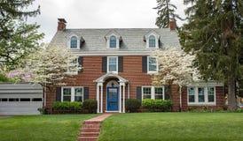 Casa con mattoni a vista con gli alberi di corniolo di fioritura Fotografia Stock Libera da Diritti