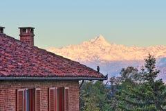 Casa con mattoni a vista e montagne nevose in Italia. Fotografie Stock