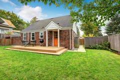 Casa con mattoni a vista esteriore con la piattaforma di legno dell'uscire in segno di disapprovazione Fotografia Stock Libera da Diritti