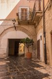 Casa con mattoni a vista gialla italiana antica con l'arco e vaso e lanterna dell'albero Iarda medievale con il balcone e l'alber fotografie stock